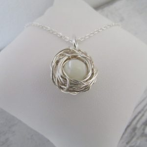 Mother of Pearl Single Egg Nest Necklace wrapped around a silver wire nest attached to an 18inch inch silver trace chain