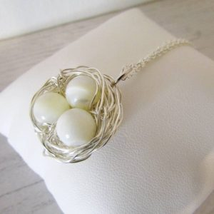 Mother of Pearl Three Egg Nest Necklace three gemstone beads tightly wrapped together with silver wire to form a birds nest. Charm attached to an 18 inch trace chain